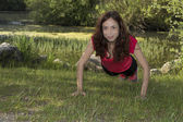 Strong fitness woman doing push-ups in nature — Stock Photo
