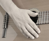 Hand on guitar strings — Stockfoto