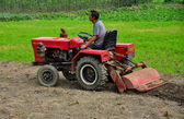 China: Farmer on Tractor Plowing Field — Stock Photo