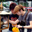 Bangkok, Thailand: Men Lighting Incense Sticks at Erawan Shrine — Stock Photo