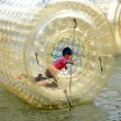 Pengzhou, China: Boy Playing Inside Inflated Plastic Water Drum — Stockfoto
