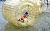 Pengzhou, China: Boy Playing Inside Inflated Plastic Water Drum — Stock Photo