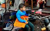 Pengzhou, china: kleine jongen zitten in het eten van de kar van de fiets — Stockfoto