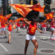 NYC:  Marchers Twirling Orange Flags at Gay Pride Parade — Stock Photo