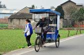 China: menina de escola deixando o triciclo na estrada rural em pengzhou — Fotografia Stock