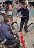 Pengzhou, China: Mechanic Fixing Bicycle Taxi Tire — Stock Photo