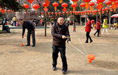 Pengzhou, China: Man Spinning Ti Huang Top in City Park — Stock Photo