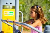 Beautiful blond hair girl playing in the playground — Stock Photo