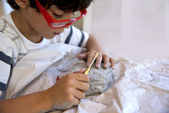 Boy excavating dinosaur fossil out of plaster — Stock Photo