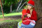 Schönes Mädchen mit roten häkeln Hut holding großen Filz Herz Valentinstag — Stockfoto