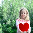 Beautiful blond girl sittig o a tree branch holding large felt heart in her hands — Stock Photo #39300079