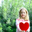 Beautiful blond girl sittig o a tree branch holding large felt heart in her hands — Stock Photo #39300245