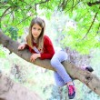 Beautiful blond girl sitting on a branch — Stock Photo