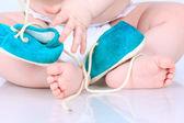Bliska małe stopy i ręce, trzymając małe buty — Zdjęcie stockowe