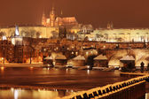 Night colorful snowy Prague gothic Castle with Charles Bridge, Czech republic — Stock Photo