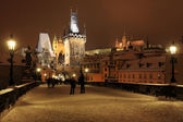 Noční romantické barevné zasněžené praze gotický hrad, mosteckou věž a katedrálu svatého mikuláše z karlova mostu, česká republika — Stock fotografie