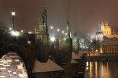 Night snowy Prague Bridge Tower and St. Nicholas' Cathedral from Charles Bridge — Stock Photo