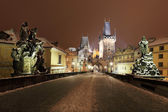 Night snowy Prague Bridge Tower and St. Nicholas' Cathedral from Charles Bridge — Stock Photo