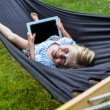 Stock Photo: Child laying in hammock with tablet