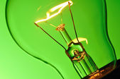Close up glowing light bulb on green background — Zdjęcie stockowe
