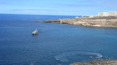Excursion ship passing between Playa Paraiso and La Caleta en Tenerife island. Canary islands. Spain. — Wideo stockowe