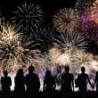 Group of people looks beautiful colorful holiday fireworks — Stock Photo