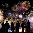 Group of people looks beautiful colorful holiday fireworks — Stock Photo #33351133