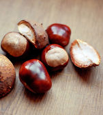 Chestnuts scattered on the table — Stock Photo