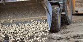 Excavator pours stones — Stockfoto
