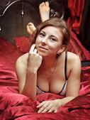 White Caucasian woman lies awake in bed red — Stock Photo