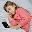 Little girl waiting for a call on the phone — Stock Photo