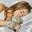 Beautiful girl lies and sleeps on a white bed — Stock Photo