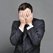 Joven esconde su rostro sobre un fondo gris — Foto de Stock