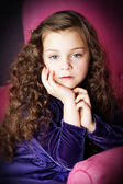 Little girl with beautiful hair posing in chair — Stock Photo