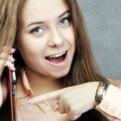 Girl speaks by mobile phone and shows it — Foto Stock