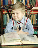 Boy sitting at a table with a big book — Stockfoto