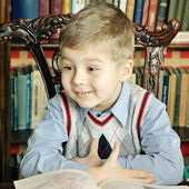 Boy sitting at a table with a big book — Стоковое фото