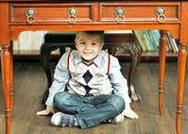 Boy sitting on the floor cross-legged — Stock Photo
