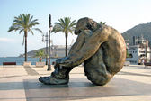 Sculpture of a seated man in the port of Cartagena — Stock Photo