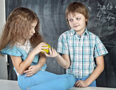Boy gives a girl an apple at school  — Stockfoto