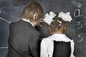 Boy and girl writing on blackboard — Stock Photo