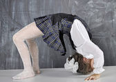 Schoolgirl doing gymnastics on the table — Stock Photo