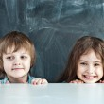 Boy and girl hiding behind a table near the school board — Stock Photo