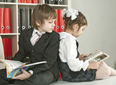Boy and girl sitting on a desk at school — Stock Photo