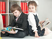 Boy and girl sitting at a table in the school — Foto Stock