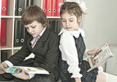 Boy and girl sitting at a table in the school — Stockfoto