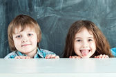 Boy and girl hiding behind a table near the school board — Foto de Stock
