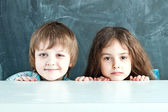 Boy and girl hiding behind a table near the school board — Stok fotoğraf