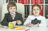 мальчик и девочка сидит за столом в школьников с книгами — Стоковое фото