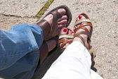 Male and female feet resting — Stockfoto